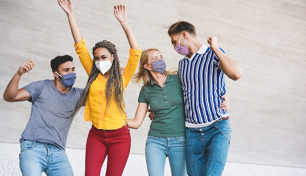 Молодые люди веселятся на городской улице во время вспышки коронавируса - основное внимание уделяется лицу блондинки