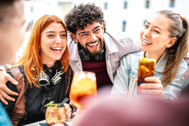 Young people having fun drinking at open air bar after work