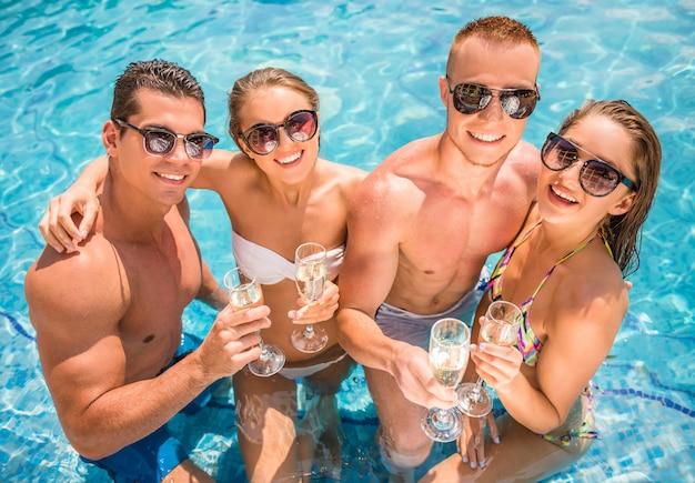 Молодые люди веселятся в бассейне.