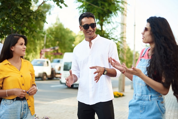 屋外で楽しんでいる若者。多民族の友人のグループが話している