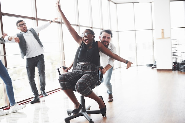 Young people having fun in the spacey office room riding the afro american oman on the chair
