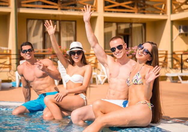 Young people having fun in swimming pool, smiling.