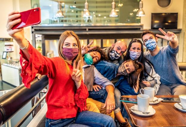 Молодые люди веселятся, делая селфи в кафе-ресторане