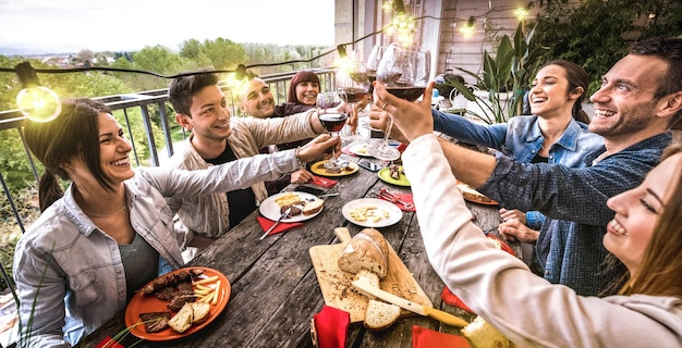 屋外の別荘でのディナーパーティーで一緒に赤ワインを乾杯するのを楽しんでいる若者