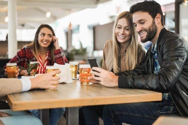 Молодые люди веселятся, используя мобильный телефон, попивая пиво в баре-ресторане - сосредоточьтесь на лице человека