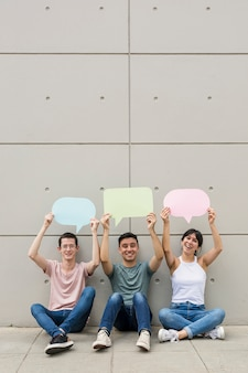 Young people holding colorful speech bubbles