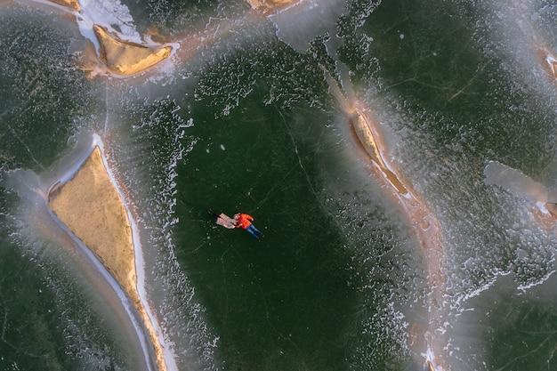 ダウンジャケットを着た若者たちは、凍った砂場の氷の上に横になります。上からの眺め