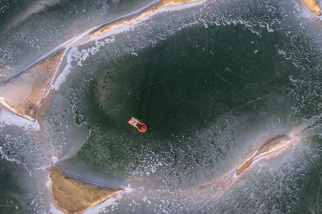 ダウンジャケットの若者が凍った砂場の氷の上に横たわる