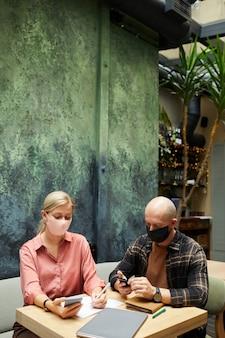 テーブルに座って、カフェでの会議中にスマートフォンを使用してマスクをしている若者