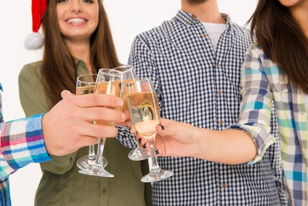 シャンパンでクリスマスを祝うサンタの帽子をかぶった若者