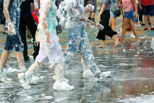 젖은 길을 걷는 비누 거품에 젊은 사람들