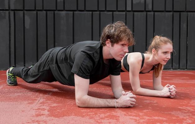 Молодые люди в спортивной одежде тренируются на открытом воздухе
