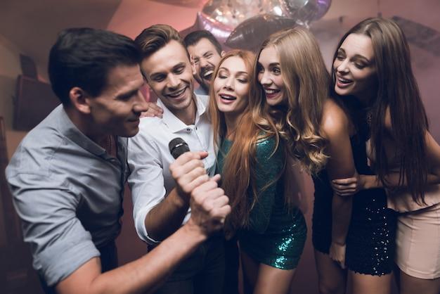 Молодые люди в клубе танцуют и поют.