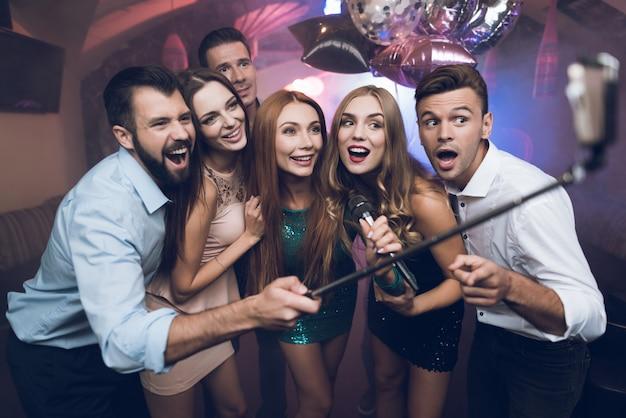Молодые люди в клубе поют песни, танцуют и делают селфи.
