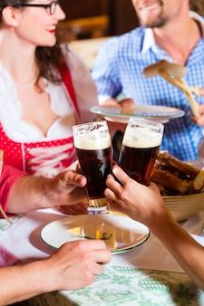 레스토랑이나 펍 점심 또는 저녁 식사에서 소시지와 함께 먹는 전통적인 바이에른 트라 흐트의 젊은이들