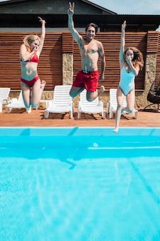 젊은 사람들이 수영장에서 점프