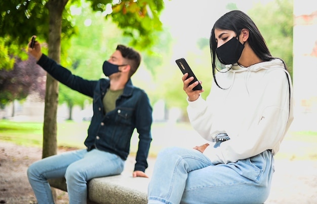 Young people keeping social distancing due to coronavirus while using their phone outdoor in a park