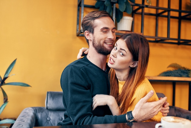 Young people in love hugging while sitting at a table in a cafe and orange wall interior