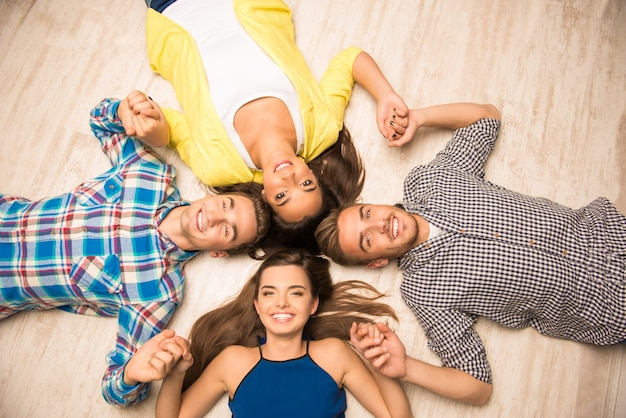 Young people lying on the floor holding hands