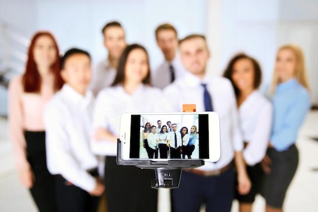 사무실에서 스마트 폰으로 단체 사진을 만드는 젊은 사람들