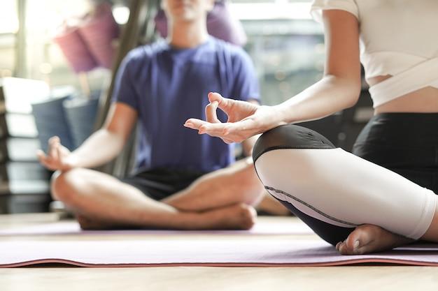 Молодые люди делают позу лотоса медитации в тренажерном зале, йога и фитнес концепции
