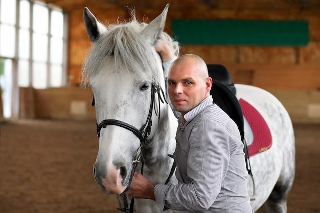 Молодые люди на лошади тренируются на деревянной арене