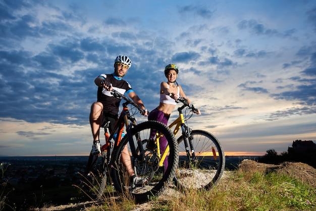 일몰 마법의 하늘 아래 언덕 위에 산악 자전거에 젊은 사람들.