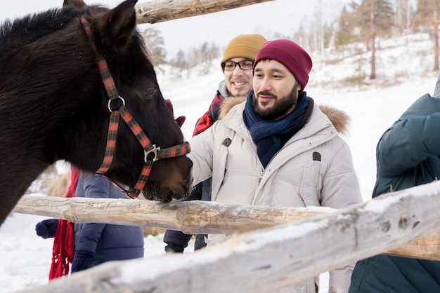 Young people petting horses on ranch