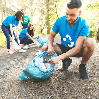 Young people picking garbage in woods Premium Photo