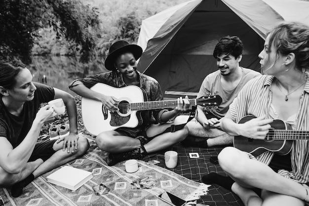Молодые люди играют на гитаре в лесу