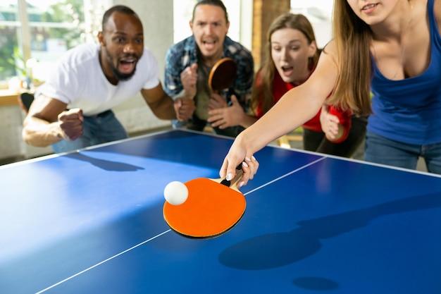 젊은 사람들은 직장에서 탁구를 치고 즐겁게 놀고 있습니다. 캐주얼한 옷을 입은 친구들은 화창한 날에 함께 탁구를 칩니다. 여가 활동, 스포츠, 우정, 팀 빌딩, 팀워크의 개념.
