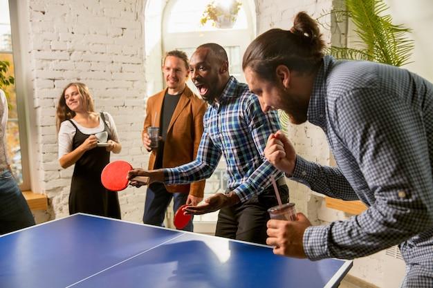 Молодые люди играют в настольный теннис на рабочем месте, весело. друзья в повседневной одежде вместе играют в настольный теннис в солнечный день. концепция досуга, спорта, дружбы, тимбилдинга, совместной работы.