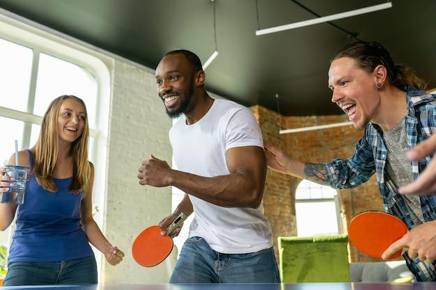 Молодые люди играют в настольный теннис на рабочем месте, веселятся