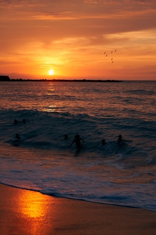 Young people playing with the waves at sunset