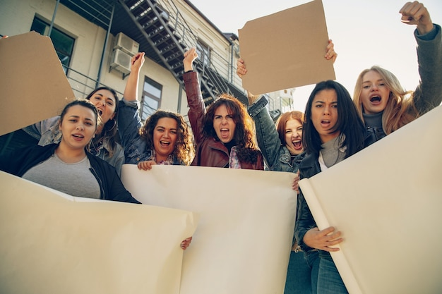 Young people protesting of women's rights and equality on the street. caucasian women have meeting about problem in workplace, male pressure, domestic abuse, harassment. copyspace. holding posters.