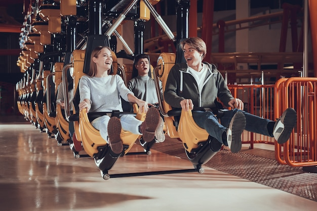 Young people raise their feet while sitting on the carousel