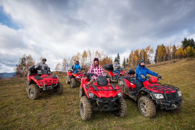 Young people on red atv off-road vehicles on a countryside trail in nature under the sky with clouds