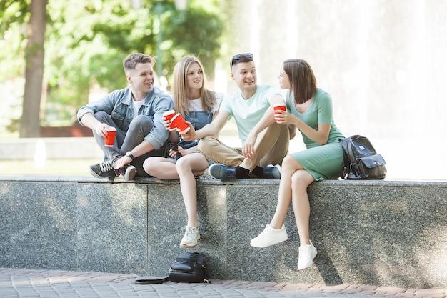 분수 근처에서 휴식하는 젊은 사람들. 함께 시간을 보내는 친구의 그룹입니다. 친구는 재미.