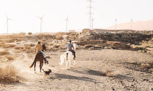 Young people riding horses in desert