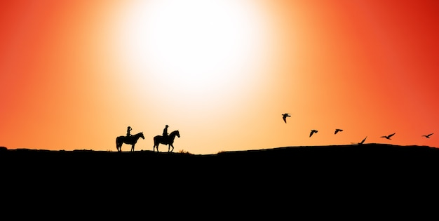 Young people riding horses at sunset time