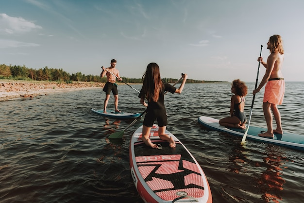 Young people rowing surfs in sea with paddles.