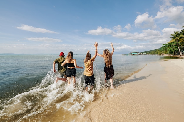 Молодые люди бегают и плещутся на пляже