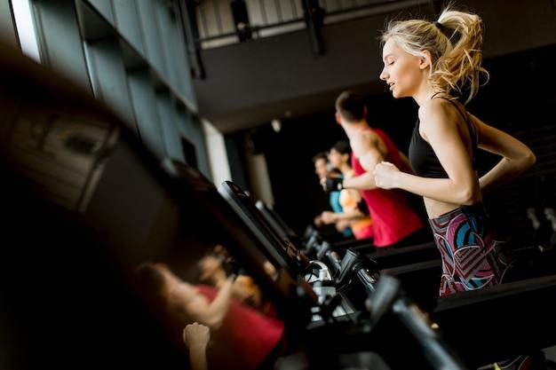Молодые люди бегут на беговых дорожках в современном тренажерном зале