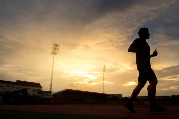 Young people runs at the stadium on beautiful sunset.