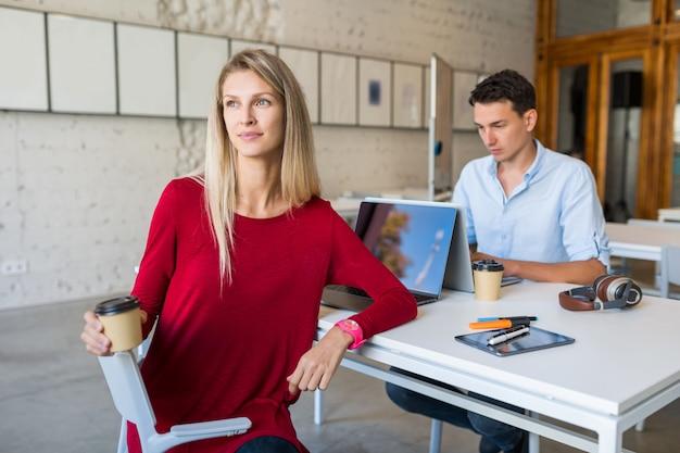 テーブルに座って、コワーキングオフィスのラップトップで働く若者たち