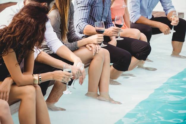 Молодые люди сидят у бассейна, пьют, веселятся, отдыхают