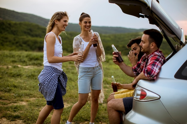 Young people sitting in the car trank during trip in the nature