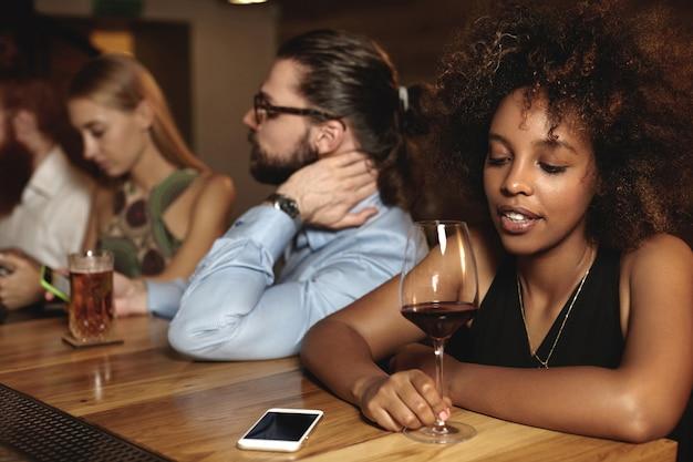 バーに座って飲み物を飲む若者
