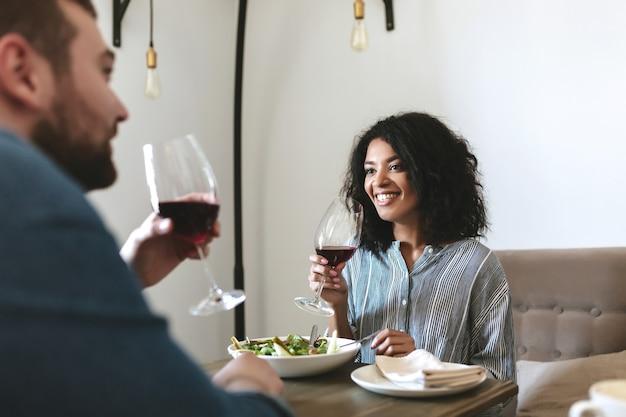 레스토랑에 앉아 레드 와인을 마시는 젊은 사람들. 샐러드를 먹고 카페에서 와인을 마시는 아름다운 흑인 소녀