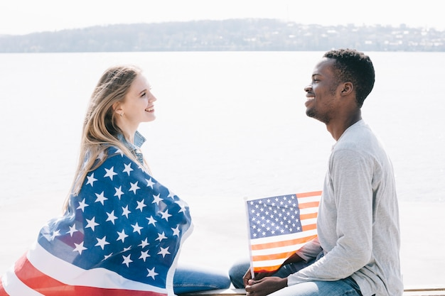 Young people sitting on sea shore and smiling together holding american flag